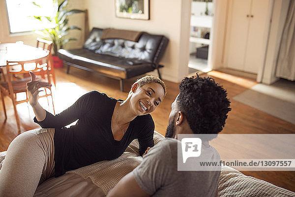 Schrägansicht einer glücklichen Frau im Gespräch mit einem Mann im Schlafzimmer