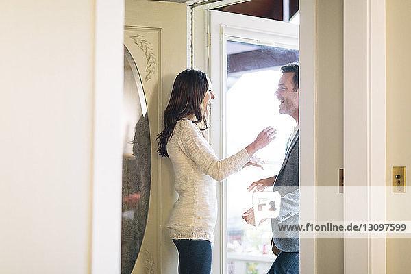 Happy woman looking at man while standing in doorway