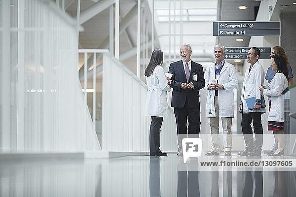 Leitender Arzt diskutiert mit Kollegen  während er im Krankenhauskorridor steht