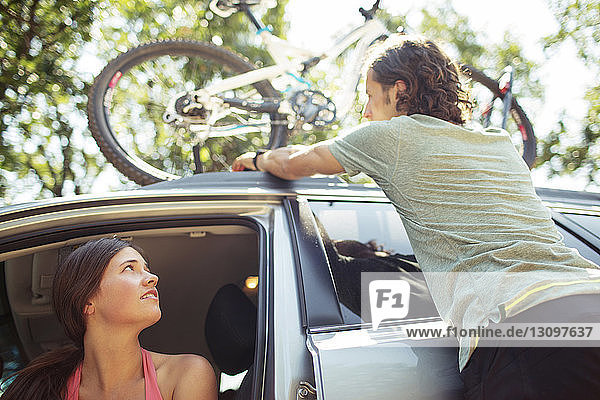Woman looking at man standing by car with bicycle on roof