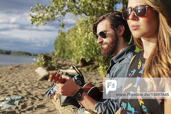 Woman sitting with friend playing ukulele