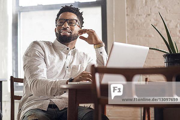 Glücklicher Mann schaut weg  während er den Laptop am Tisch benutzt