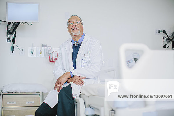 Male doctor sitting on bed in hospital ward