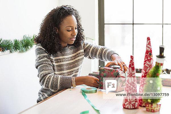 Frau packt Weihnachtsgeschenk ein  während sie zu Hause sitzt