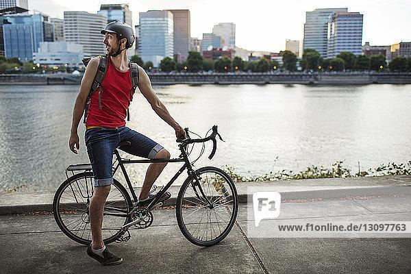 Radfahrender Sportler auf der Straße am See in der Stadt