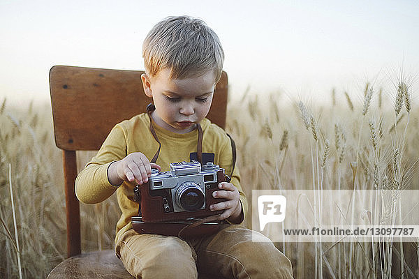 Cute boy with vintage camera sitting on chair amidst wheat field