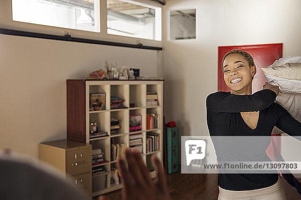 Fröhliche junge Frau wirft zu Hause Kissen auf Mann