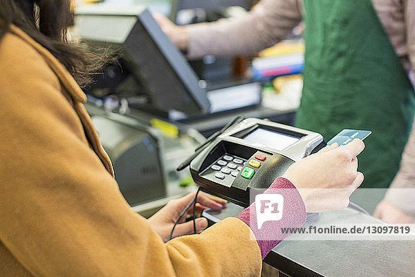 Mittelsektion einer Frau  die im Supermarkt eine Rechnung mit Kreditkarte bezahlt