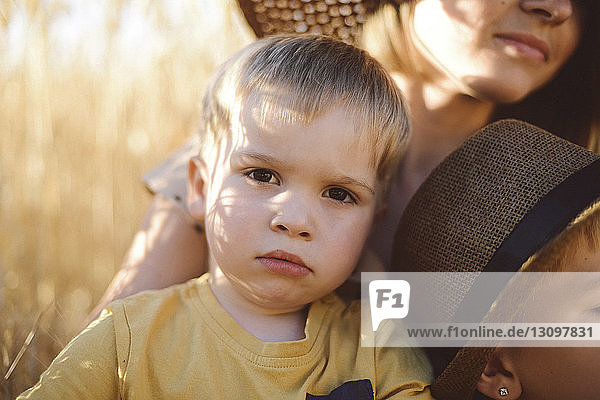 Portrait of cute boy with mother and brother on field