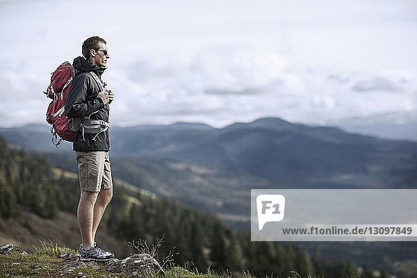 Hiker carrying backpack while standing on mountain against sky
