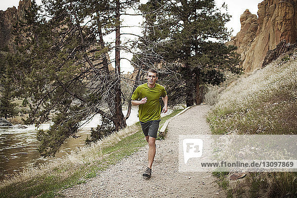 Young man running on footpath by lake