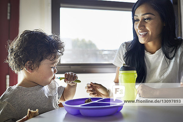 Smiling mother looking at son eating food at home