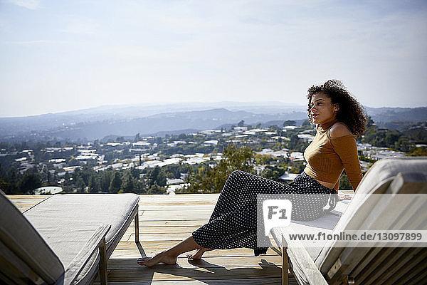 Seitenansicht einer Frau  die weg schaut  während sie auf einem Liegestuhl gegen den Himmel sitzt