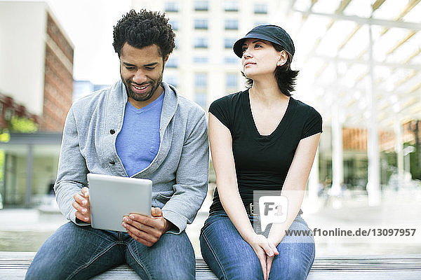 Nachdenkliche Frau sitzt neben einem Mann und benutzt einen Tablet-Computer