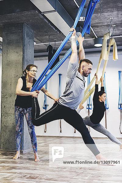 Yogalehrerin assistiert Mann  während Frau im Hintergrund im Fitnessstudio trainiert