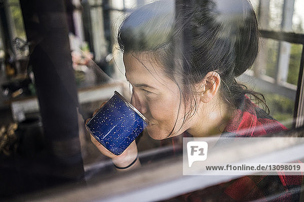 Close-up of woman drinking coffee seen through window