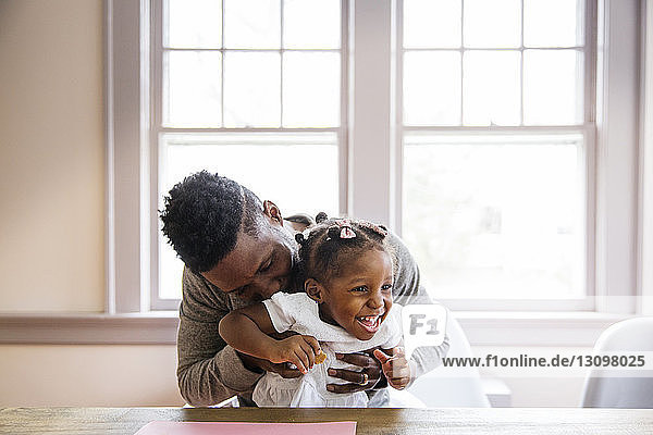 Loving father playing with cheerful girl at home