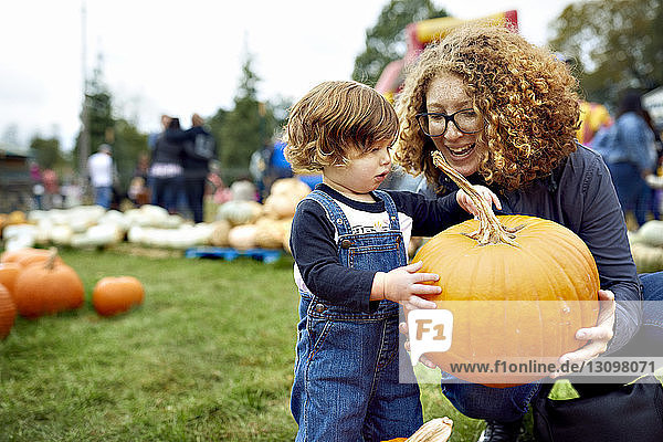 Mother with son holding pumpkin at farm
