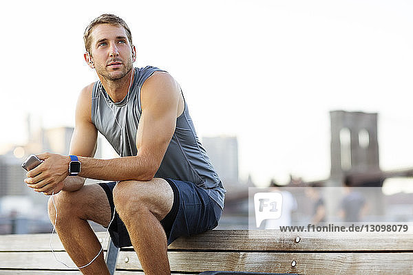 Athlete looking away while listening music on bench