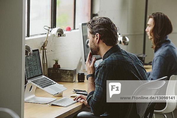 Geschäftsleute  die an Desktop-Computern bei Tisch im Büro arbeiten
