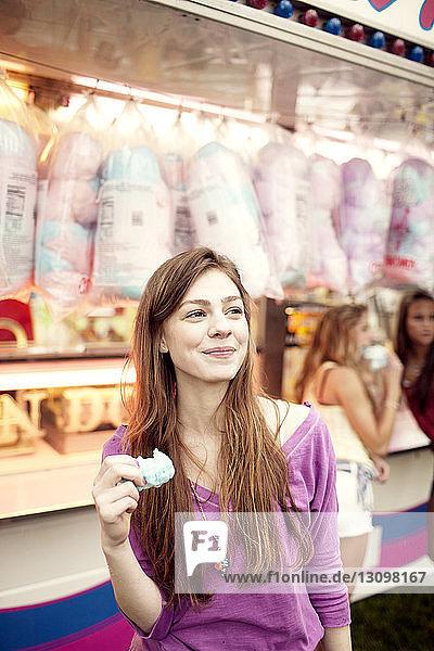 Teenager-Mädchen schaut weg  während sie Zuckerwatte am Verkaufsstand hält