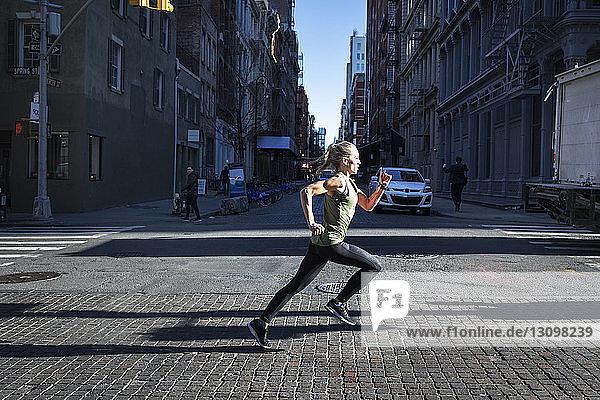 Seitenansicht einer Athletin  die an einem sonnigen Tag auf einer Straße in der Stadt läuft
