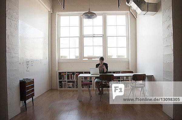 Geschäftsfrau  die in neuem Büro an Fenstern sitzt