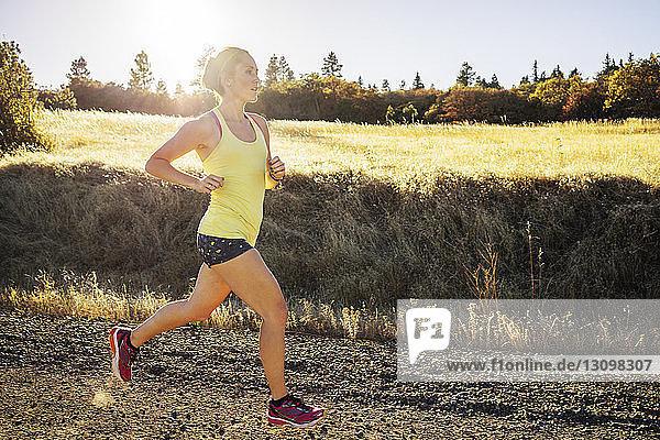 Frau in voller Länge joggt am sonnigen Tag auf dem Feld gegen den Himmel
