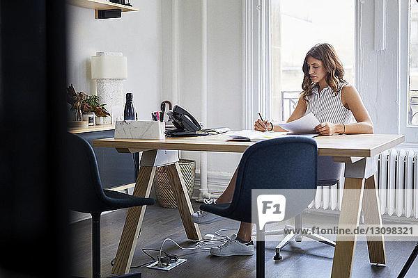 Geschäftsfrau  die mit Dokumenten arbeitet  während sie im Büro am Schreibtisch sitzt