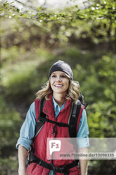 Happy woman looking away while standing in forest