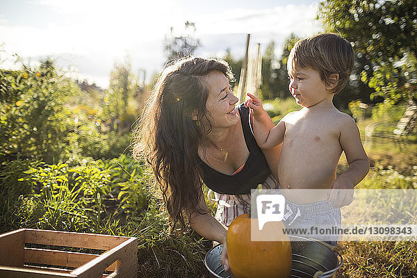 Sohn ohne Hemd spielt mit Mutter im Gemeinschaftsgarten Sohn ohne Hemd spielt mit Mutter im Gemeinschaftsgarten