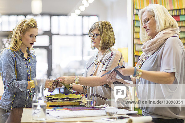 Female owners showing fabric to customer at table in furniture store