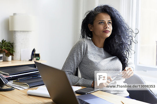 Thoughtful businesswoman looking away while sitting at desk in office