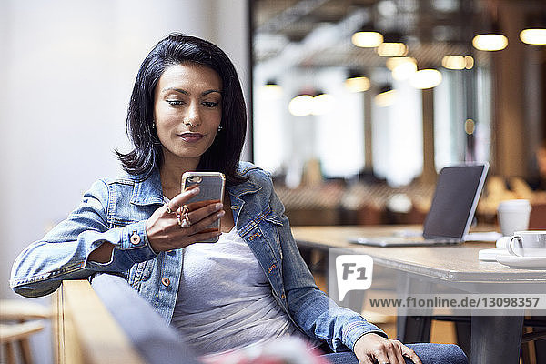 Confident businesswoman using smart phone in office