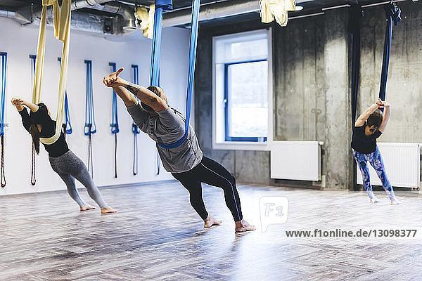Yogalehrerin unterrichtet Schülerinnen und Schüler im Fitnessstudio beim Stretching auf der Hängematte