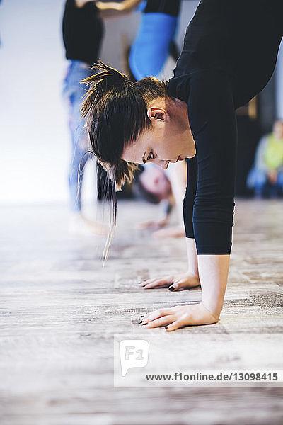 Frau übt Handstand  während der Ausbilder dem Mann im Hintergrund im Yogastudio assistiert
