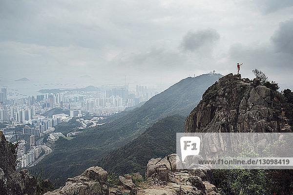 Fernansicht eines Mannes  der bei nebligem Wetter im Stadtbild auf einem Berg steht