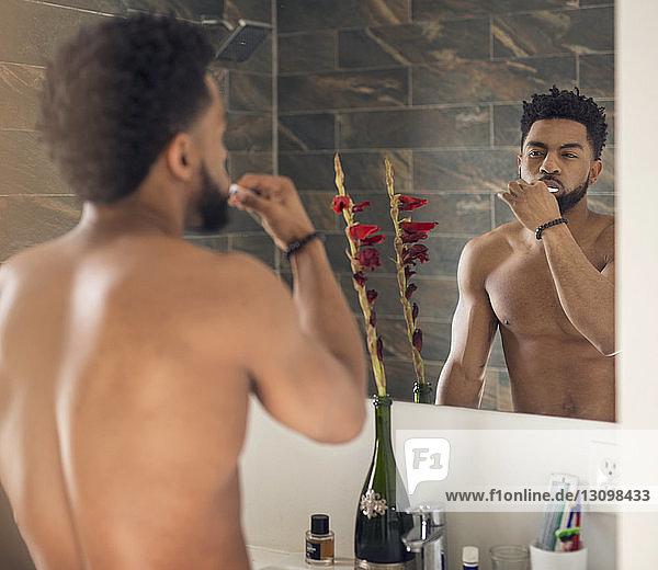 Rückansicht eines Mannes beim Zähneputzen mit einer Frau im Badezimmer