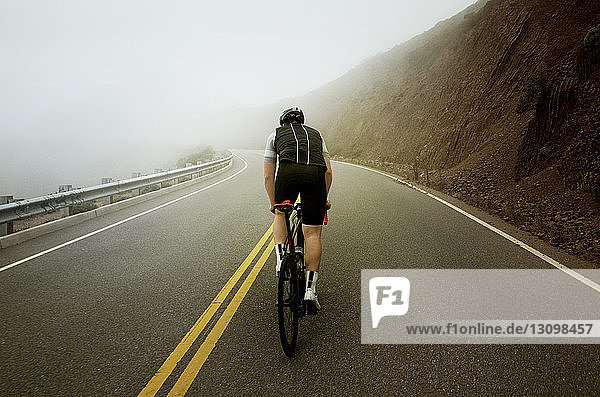 Mann fährt bei nebligem Wetter auf Bergstraßen