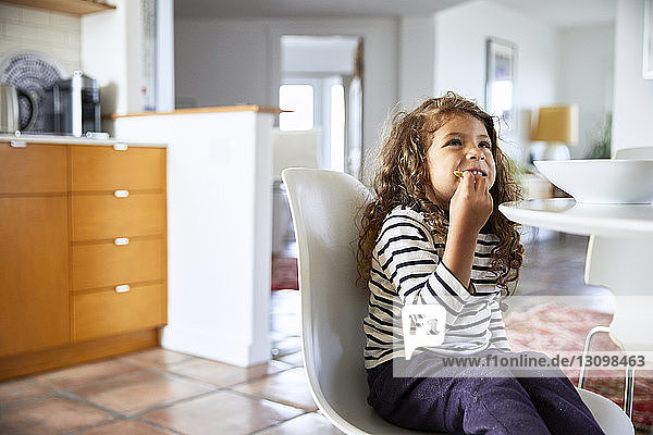 Girl looking away while eating food on chair at home