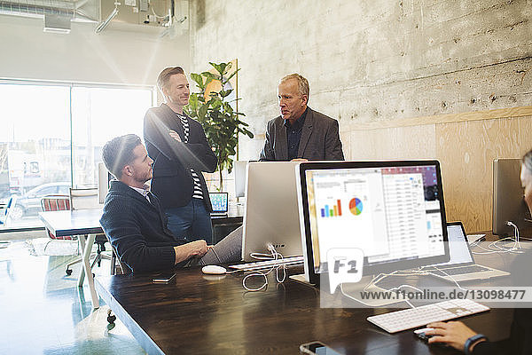 Businessmen discussing while female colleague working at desk in office