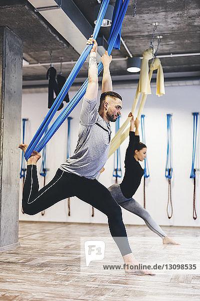 Freunde dehnen sich in Hängematten  während sie Luftyoga im Fitnessstudio praktizieren