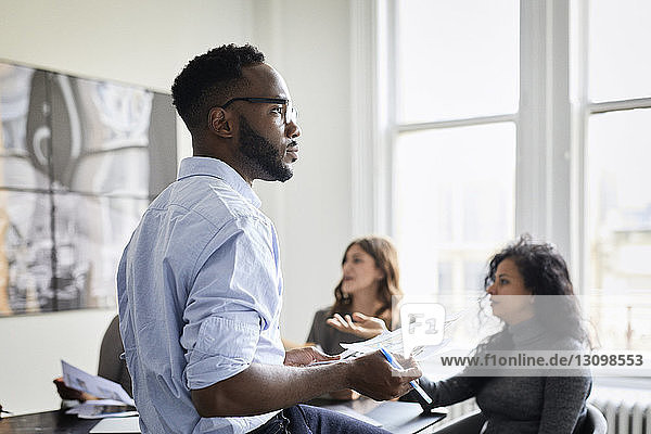 Nachdenklicher Geschäftsmann hält Dokumente in der Hand,  während weibliche Kollegen im Kreativbüro diskutieren