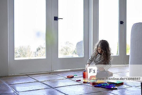 Mädchen spielt mit bunten Spielzeugbausteinen  während sie zu Hause auf dem Boden kniet