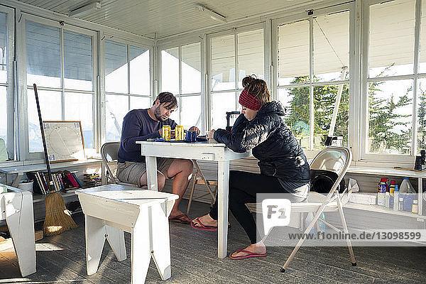 Paar liest Buch  während es in einer Hütte am Tisch sitzt
