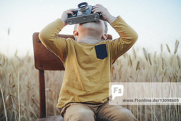 Playful boy photographing with vintage camera while sitting on chair amidst wheat field