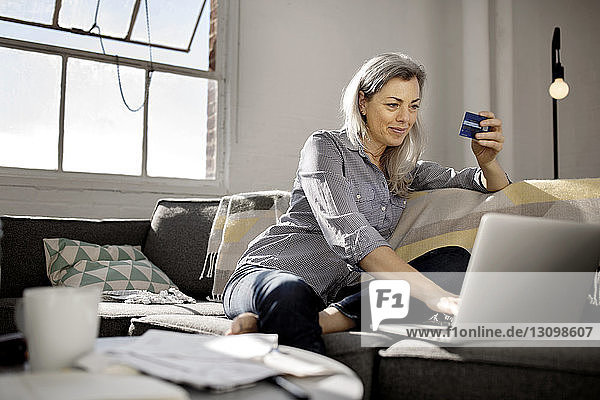 Mature woman holding debit card while using laptop on sofa