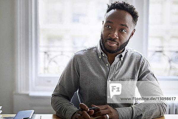 Nachdenklicher Geschäftsmann sitzt am Schreibtisch im Kreativbüro