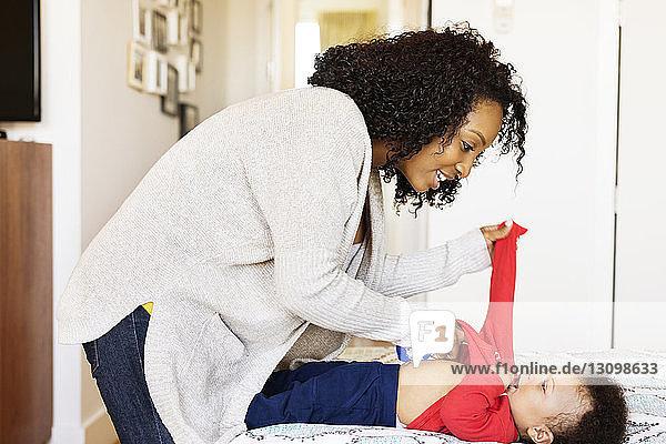 Seitenansicht einer Frau  die zu Hause dem Sohn das T-Shirt auszieht