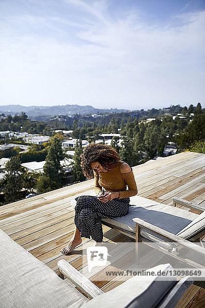 Hochwinkelansicht einer Frau  die ein Mobiltelefon benutzt  während sie auf einem Liegestuhl gegen den Himmel sitzt